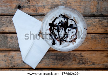 Top view of plastic cup of iced fresh milk with chocolate sauce and tissue paper on wooden table. Stock fotó ©