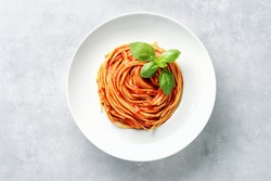 Top view of plate with spaghetti in tomato sauce and basil on white background