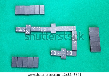 top view of playfield of dominoes board game with black tiles on green baize table