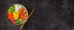 Top view of poke bowl with salmon and avocado on dark background