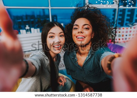 Top view of portrait of two young cheerful females making self-portrait photo. Selfie concept