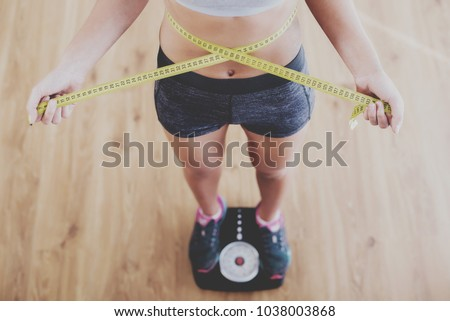 Top view of pretty slim woman with measure around her body is standing on the scales. #1038003868