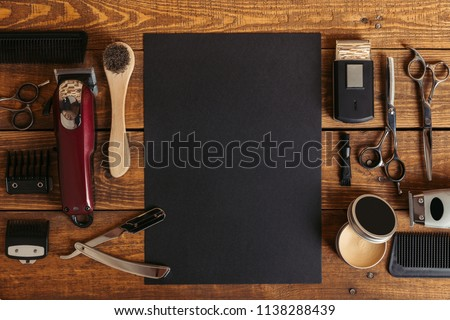 top view of professional barber tools and blank black card on wooden table