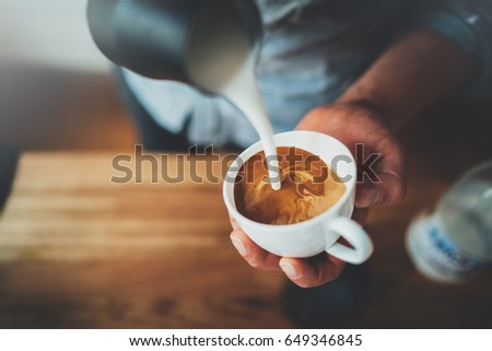 Top view of professional barista pouring milk and preparing fresh cappuccino, hot drinks and coffee preparations concept, lifestyle