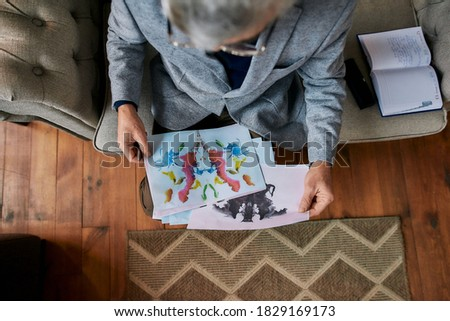 Top view of psychologist choosing picture with ink stain, Rorschach Inkblot during therapy session. Focus on picture. Horizontal shot