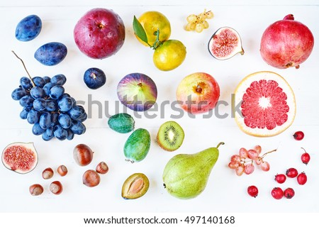 Top view of rainbow colored fruits on white table.