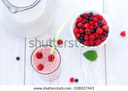 Top view of raspberry and blueberry milkshake on white wooden table