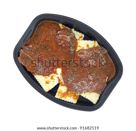Top view of ravioli and tomato sauce frozen tv dinner on a white background.