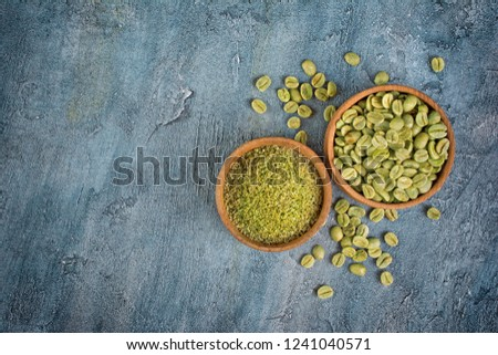 Top view of raw green unroasted coffee with ground beans in wood bowls on blue concrete background with copy space #1241040571