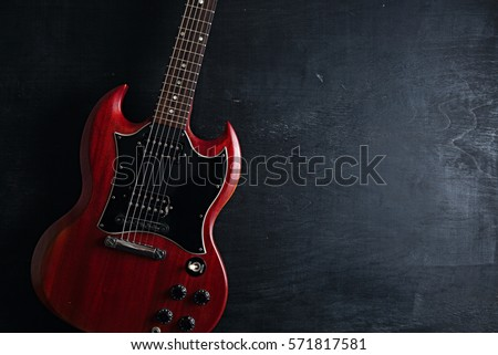 Top view of red electric guitar on dark wooden background