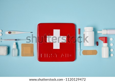 top view of red first aid kit box on blue surface with medical supplies