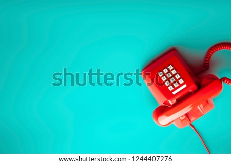 Top view of red telephone on green desk or background, waiting phone call, phone ringing, vintage, classic red telephone. #1244407276