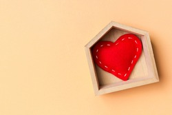 Top view of red textile heart in a wooden house on colorful background. Home sweet home concept. Valentine's day.