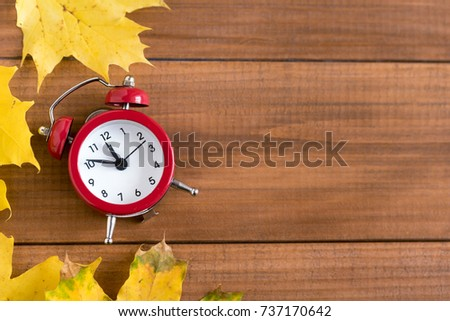 Top view of red vintage clock and mable leaf. Autumn time change