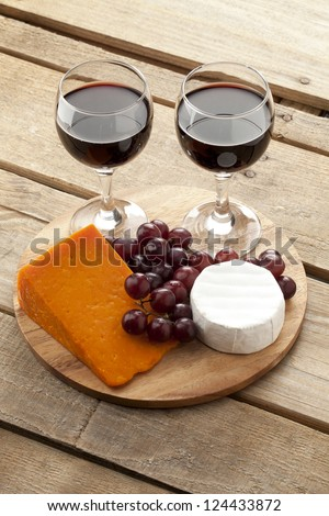 Top view of red wine, cheese and grapes on wooden plate