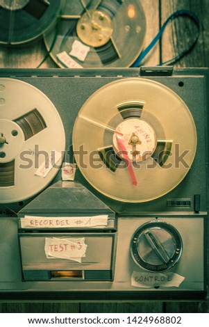 Top view of reel-to-reel tape recorder and rolls tapes #1424968802