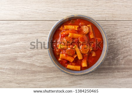 Top view of rigatoni pasta and sausage in an old stoneware bowl on a tile table illuminated with natural lighting.