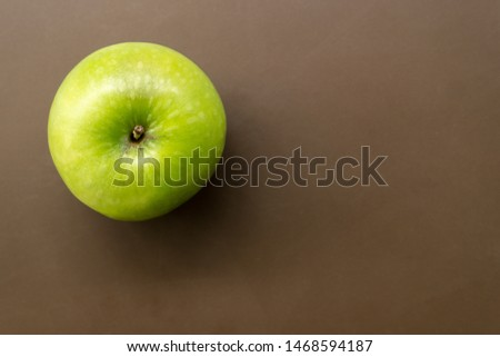 Top view of riped green apple sitting on brown bacckground.