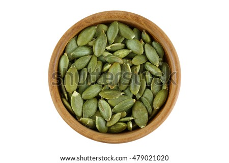 Top view of roasted pumpkin seeds in wooden bowl. Dry Pepita after shelling isolated on white background. Foto stock ©