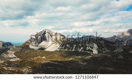 Top view of rocky terrain in green with rock. Stock. Rock mountain erosion. Beautiful view of mountains and nature. Mountain panorama against blue sky with clouds #1271106847