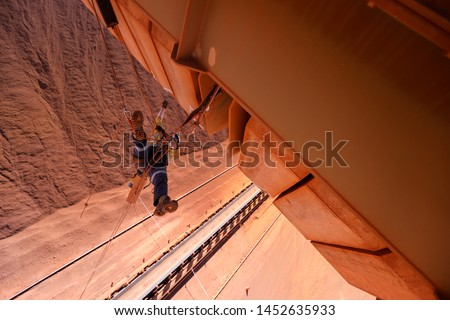 Top view of rope access worker inspector wearing fall safety harness protection working abseiling in rope transfer position conducting concrete spalling inspection on counterweight mine site