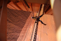 Top view of rope access worker inspector wearing fall safety harness working abseiling in rope transfer position conducting concrete spalling inspection on counter weight