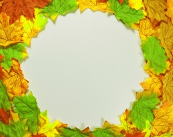 Top view of round frame formed with lots of small vibrant artificial autumn yellow leaves on white background