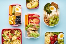 Top view of school lunchboxes with various healthy nutritious meals on blue background
