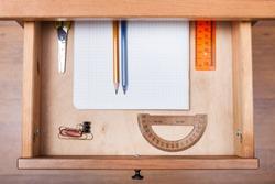 top view of school set in open drawer of nightstand