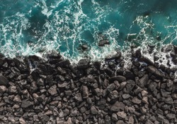 Top view of sea waves hitting rocks. Aerial view of sea water and beach coast with stones.