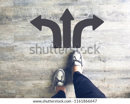 Top view of selfie feet on wooden floor background with gray drawn left, towards and right direction arrows , decision making , Choices concept, where to go, directions, business solutions #1161866647