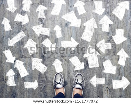 Top view of selfie feet on wooden floor background with white drawn many direction arrows , decision making , Choices concept, where to go, directions, business solutions #1161779872