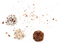 Top view of set of beautiful and delicious chocolate truffle sweets decorated with assorted wafer crumbs isolated on a white background. Closeup studio shot with soft selective focus.