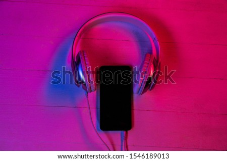 Top view of set of gadgets in purple neon light and pink background. Smartphone and headphones. Copyspace for your advertising. Tech, modern, gadgets. Music listening.