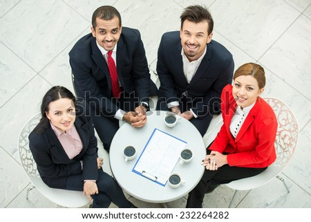 Top view of several business people are planning work at round table. They are looking at the camera.