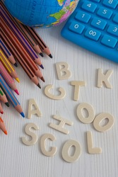 Top view of several diagonal colored pencils, world ball and blue calculator, with the words back to school unlinked, on white wooden background in vertical