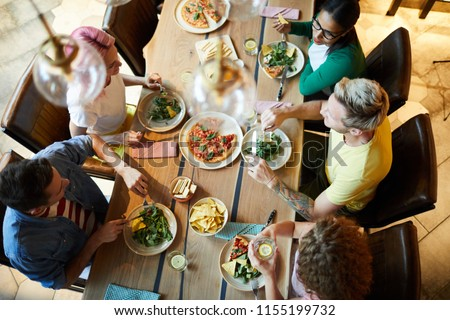 Top view of several young people sitting by wooden table served with tasty food, enjoying dinner and discussing news