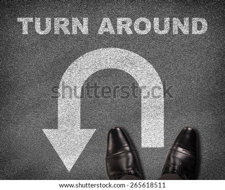 Top view of shoes standing on asphalt road with U-turn sign and text turn around. Business concept