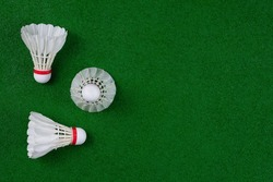 Top view of shuttlecocks arranged on a green badminton court. Flat lay with blank copy space.