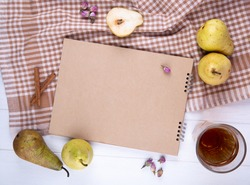 top view of sketchbook made of craft paper with fresh ripe pears and a glass of lemonade on plaid tablecloth