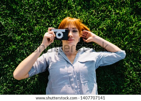 Top view of skilled amateur photographer lying on green summer grass in park and making pictures on leisure, portrait of attractive female with old fashioned equipment in hand looking at camera