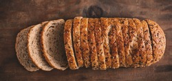 Top view of sliced wholegrain bread on dark ructic wooden  background closeup