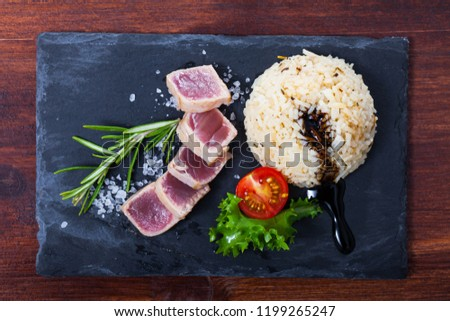 Top view of slightly fried tuna (tataki) served with spicy rice, vegetables and soy sauce on black serving board #1199265247