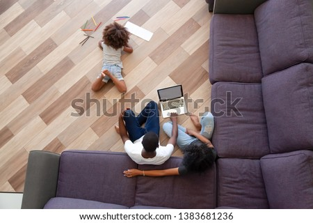 Top view of small African American girl lying on home floor painting with colorful pencils, parent sit using laptop watching movie or shopping, young black family relax together on weekend