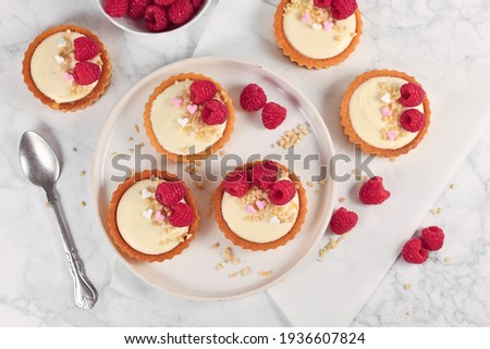 Top view of small tartlet pastries with white cream, topped with raspberry fruits and almond sprinkles