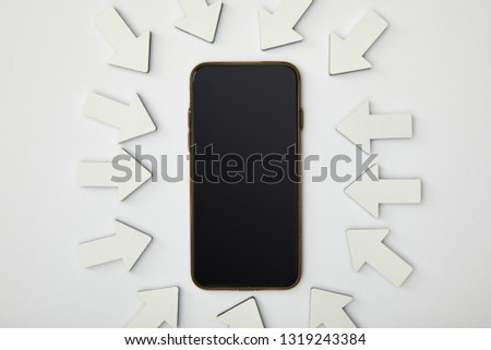 top view of smartphone in ellipse with white pointers on grey background #1319243384