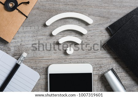 Top view of smartphone on desk searches a free wifi connection available. High angle view of smart phone with white wi-fi sign on top. Internet technology and networking concept.