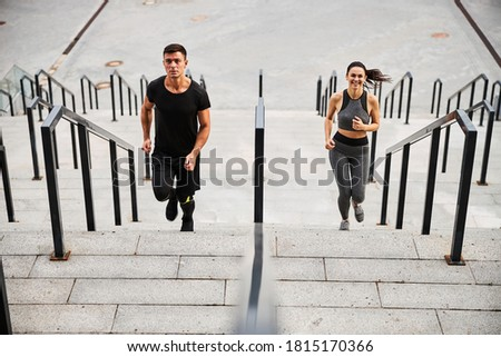Top view of smiling slim woman and athletic male in outfit running up to urban building together Foto stock ©