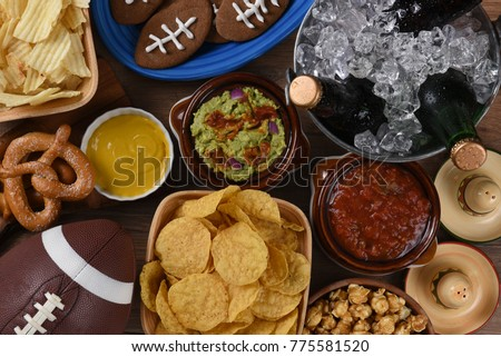 Top view of snacks and drinks laid out for a football watching party.
