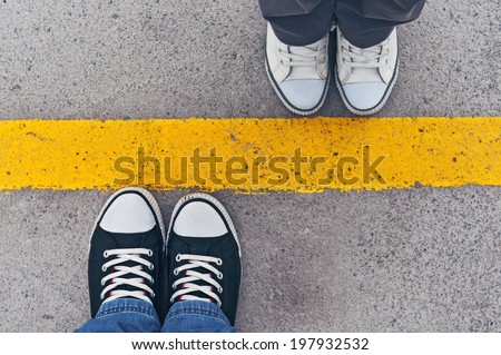 Top view of sneakers from above, male and female feet in casual footwear standing at dividing frontier line.